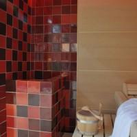 Finnische Sauna mit trendiger Ofenverkleidung aus Keramik und indirekter LED Hinterleuchtung