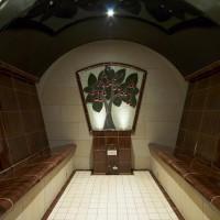 Dampfbad- mit Keramik und Fliese. Wand und Boden gefliest. Keramische Sitzbänke in Körperform. Wandbelag aus Keramik. Dampfauslass vom Dampferzeuger mit massiver Keramikplatte.