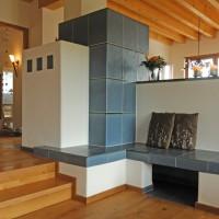Kachelofen mit keramischer Bank und großformatiger Keramik