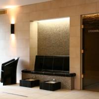 Wärmebank mit Fußbad. Eckige Keramik-Fußbecken. Nischenspiegel mit Mosaik und indirekter Beleuchtung.