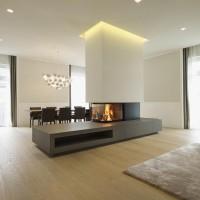 moderner, freistehender Kamin mit Sitzbank und drei Glasseiten