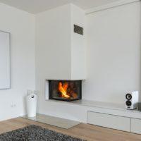 Minimalistischer Moderner Designkamin mit weißem Marmor in moderner Bauart. Verputzte Flächen mit Warmluftgitter.