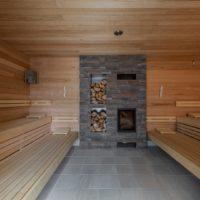 Thermalbad Aukammtal Wiesbaden: Feuersauna mit Kamin aus Naturstein und Holzlager