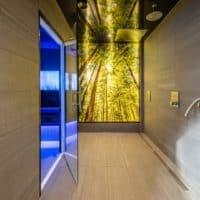 Duschbereich vor dem Dampfbad im Freizeitbad Gochness mit LED Beleuchtung Wandbild in der Dusche Dusche. Glasscheibe mit Druck hinterleuchtet.